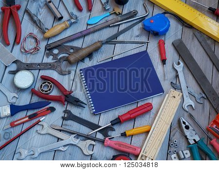 Notebook and tools on a wooden floor top view. Locksmith and carpentry tools.
