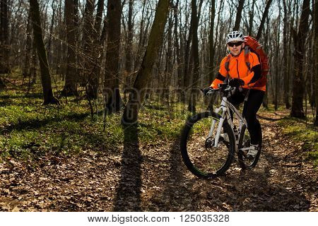 Mountain biker riding on bike in autumn inspirational mountains landscape. Man cycling MTB on enduro trail track. Sport fitness motivation and inspiration. ** Note: Soft Focus at 100%, best at smaller sizes