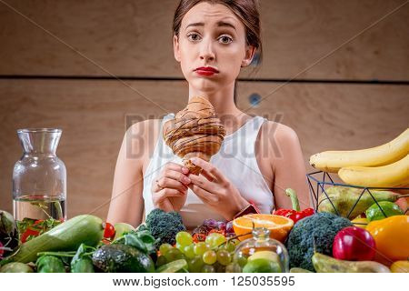 Young woman feeling sorry for eating sweet croissant instead of healthy fruits and vegetables. Worry about calories and weight