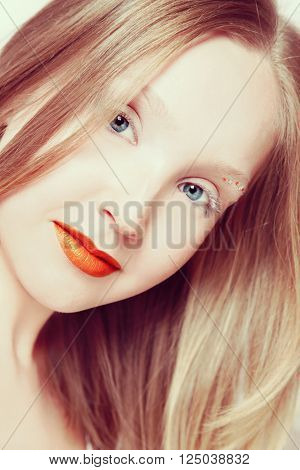 Vintage style portrait of young beautiful smiling blond girl with orange lipstick and fancy make-up, selective focus