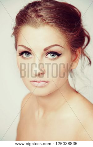 Vintage style portrait of young beautiful woman with eyebrows tattoo and hair bun, selective focus