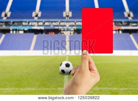 Football referee showing you the red card and expelled with stadium background