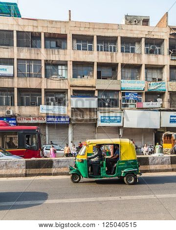 DELHI INDIA - 19TH MARCH 2016: Tuk Tuk Rickshaws on a street in central Delhi during the day. People and buildings can be seen.