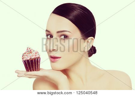 Vintage style portrait of young beautiful girl with excited expression and tasty cupcake in her hand