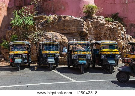 JAIPUR INDIA - 22ND MARCH 2016: Tuk Tuk Rickshaws parked outside in a rural area in Jaipur India. People can be seen.