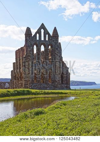 Whitby Abbey and North Sea in North Yorkshire in England. It is ruins of the Benedictine abbey. Now it is under protection of the English Heritage.