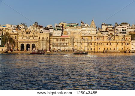 UDAIPUR INDIA - 20TH MARCH 2016: A view of part of the Udaipur Skyline during the day. Boats buildings and people can be seen.