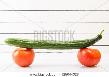 Two ripe tomatoes with cucumber against a light background propped up