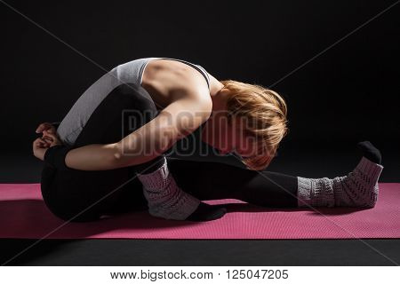 Young woman practicing yoga, Marichyasana / Forward bend pose
