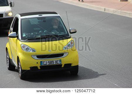 Monte-Carlo Monaco - April 6 2016: Yellow Compact Car Smart Fortwo on Avenue d'Ostende in Monaco. Man Driving a Yellow Car Smart Fortwo in the South of France