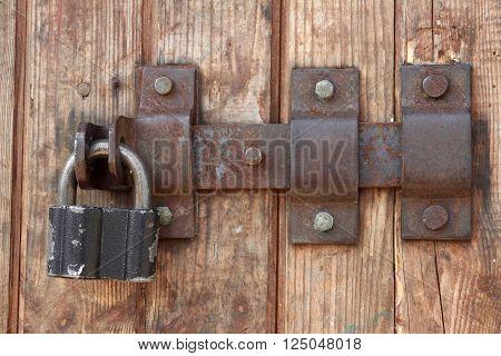 Old doors lock on wood barn background