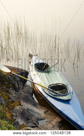 Kayak with oar and fishing-tackle rests on shore of lake in summer