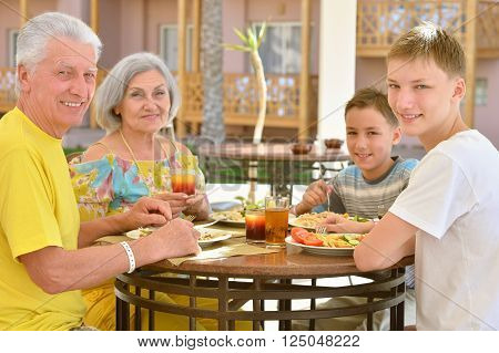 Grandparents with grandchildren at breakfast on tropical resort