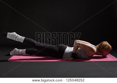 Young woman practicing yoga, Salabhasana / Locust pose