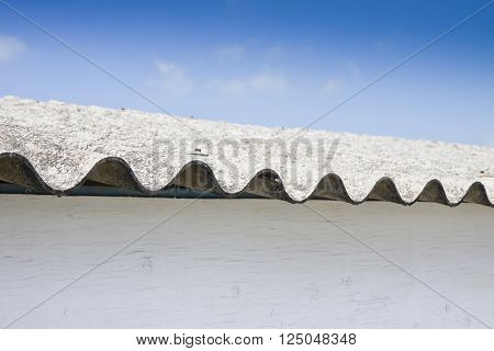 Detail of a dangerous asbestos roof against a blue sky