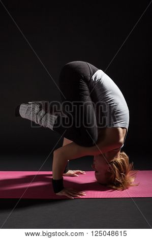 Young woman practicing yoga, Sirsasana / Supported Headstand pose