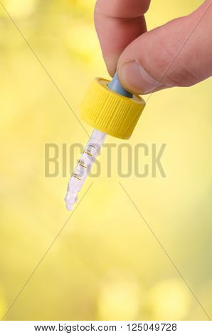 Hand keep a dropper on a natural background. Green background. Medicine, aromatherapy. Dropping pipette.