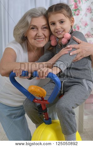 senior woman and  little granddaughter doing exercise at  home