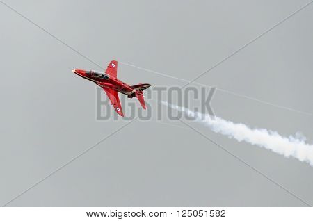 HEADCORN, KENT, ENGLAND - 15 AUGUST 2015: A single Red Arrow aeroplane in flight with white vapour emitting from it's tail end