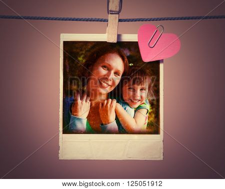 Mom and daughter instant photo and small red paper heart hanging on the clothesline. Photos in grunge style.