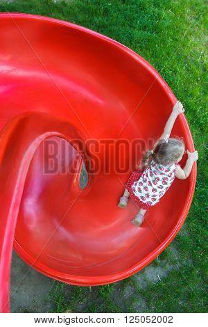 Overhead shot of little blonde girl is sliding down red plastic spiral playground slide