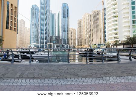 cityscape, travel, tourism and urban concept - Dubai city seafront or harbor with boats