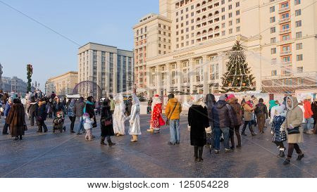 Moscow - January 7 2016: Happy people and tourists walk on Manezhnaya Square during the winter holidays and Christmas Santa Claus with two Snow Maiden January 7 2016 Moscow Russia