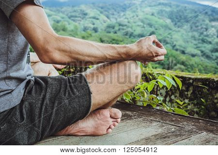 Young man meditating in the gazebo on the background of the mountains in Bali