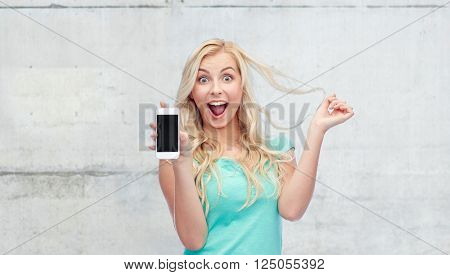 emotions, expressions, technology and people concept - smiling young woman or teenage girl showing blank smartphone screen over gray concrete wall background