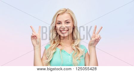 positive gesture and people concept - smiling young woman or teenage girl showing peace hand sign with both hands over rose quartz and serenity gradient background