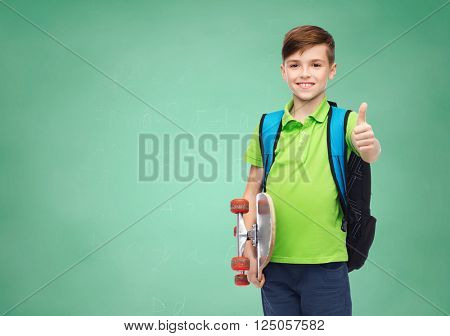 childhood, gesture, education and people concept - happy smiling student boy with backpack and skateboard showing thumbs up over green school chalk board background
