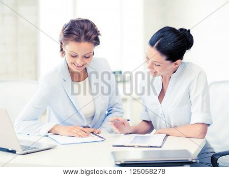 picture of two smiling businesswomen working in office
