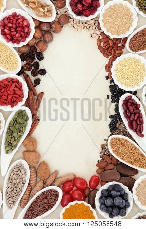Super food border in porcelain dishes over parchment paper background. High in vitamins and antioxidants.
