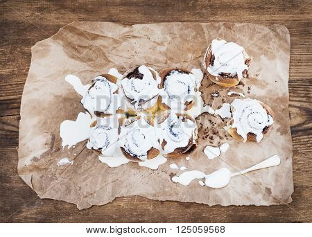 Cinnamon rolls with cream cheese icing on piece of oily craft paper over rustic wooden background, top view