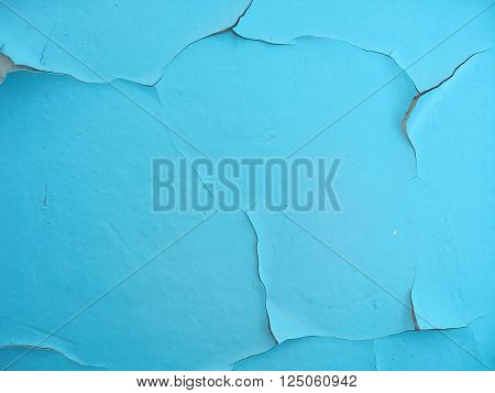 Close-up of blue cracked paint on the wall. Old weathered painted wall surface. Grunge background with vintage paint