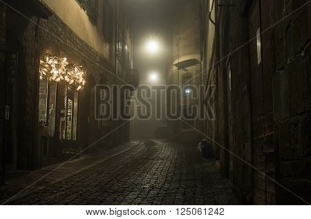Old European narrow empty street of a medieval town on a foggy evening. Taken in Bergamo, Citta Alta
