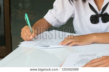 Thai students writing on a paper for exams and admissions in high school, Thailand