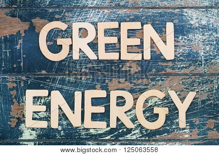 Green energy written with wooden letters on rustic surface