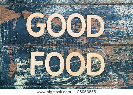 Good food written with wooden letters on rustic surface