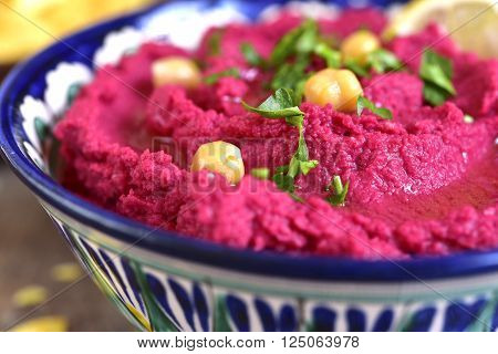 Beetroot hummus in a colorful bowll on a wooden table.