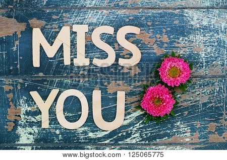 Miss you written with wooden letters on rustic surface and pink daisy flowers