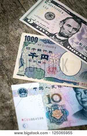 three different bank notes from china japan and usa on a wooden background vertical