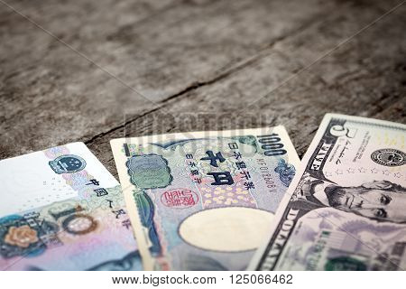 three different bank notes from china japan and usa on a wooden background horicontal