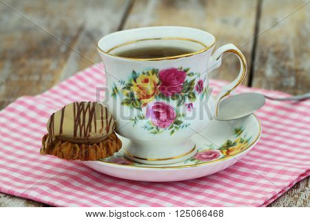 Tea in colorful vintage porcelain cup with chocolate and toffee crunchy cookie