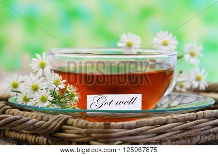 Get well card with cup of tea and chamomile flowers