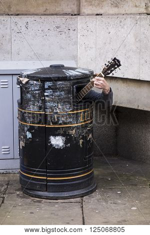 CAMBRIDGE, ENGLAND - MAY 9, 2015: A street musician plays guitar from the unusual location of the inside of a trash bin near Cambridge University in England.