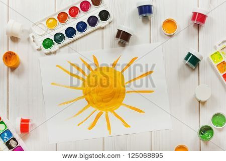Drawing sun on the desktop a top view. Education and art creative concept.