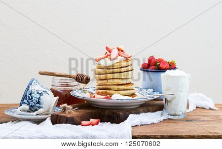 Breakfast set. Pancake tower with fresh strawberries, sour cream and honey on a porcelain plate over rustic wooden table. Blue enamel cup full of berries behind, white background, selective focus