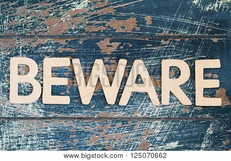 Word beware written with wooden letters on rustic surface