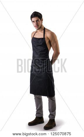 Sexy shirtless young chef or waiter posing, wearing black apron on naked body, isolated on white background